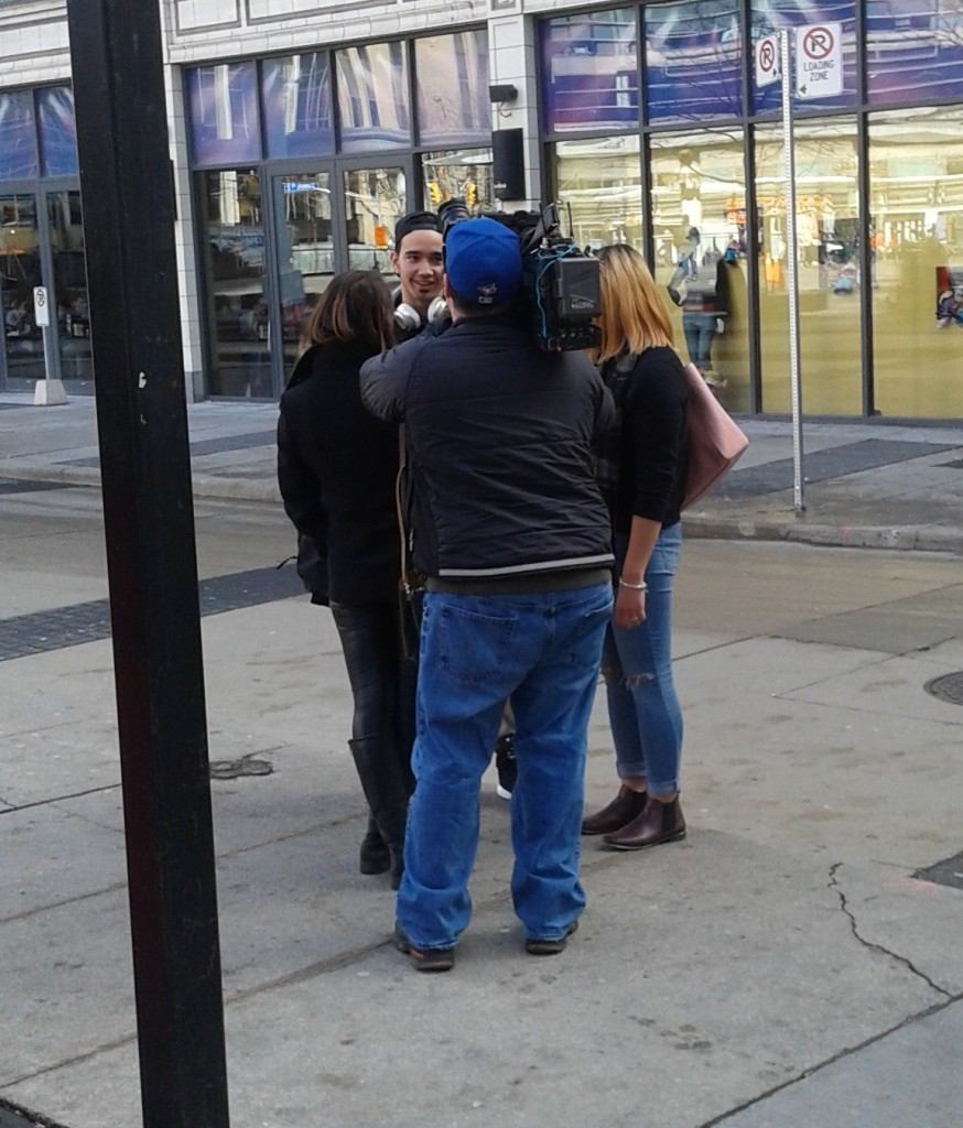Camera man with reporter conducting street interview