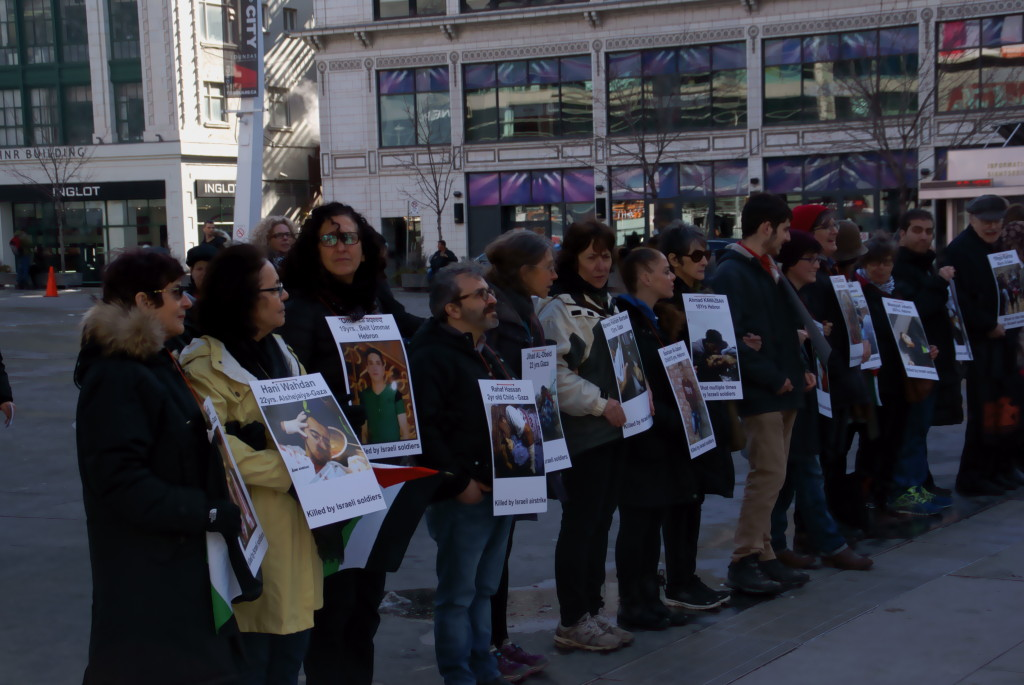Line of people along Dundas Square wearing placard with pictures of those killed by Israelis
