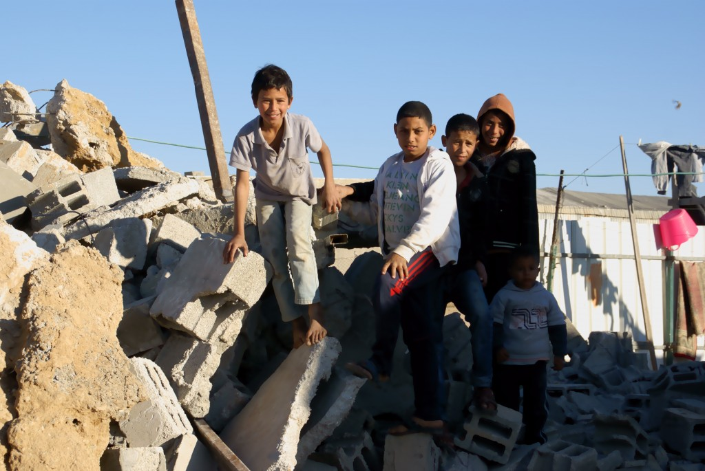 Children standing on the rubble of their demolished home in A-Za'arura